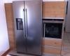 Encastrement d'un frigo dans du mobilier de cuisine par Ateliers Moinard, cuisiniste à Saint Philbert de Grand Lieu